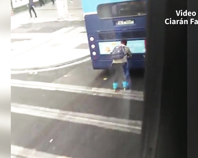 A rollerblader hanging onto the back of a Dublin bus.