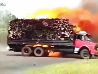 Truck full with timber on fire.