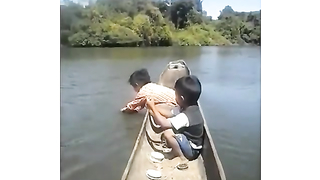 Strong little boy pulling up big fish.